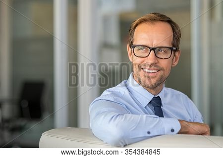 Portrait of mature bnusinessman developing a new idea at office. Happy smiling business man sitting on couch looking away with copy space. Mid man thinking about new strategy and planning the future.