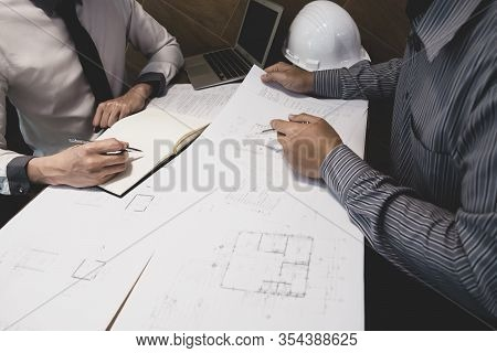 The Engineer And Partner Are Discussing About Construction Plan At The Office