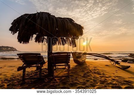 Chaises Longues On The Beach At Sunset. Tropical Resort