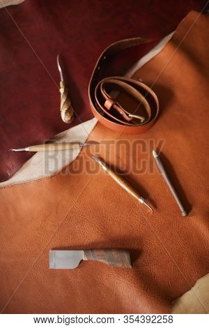 Vertical From Above Flat Lay Shot Of Various Tools For Craftwork With Leather Materials On Table