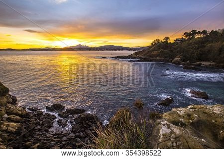 Playa De Los Frailes In The Orange Sunrise Of The Town Of Fuenterrabia. Basque Country