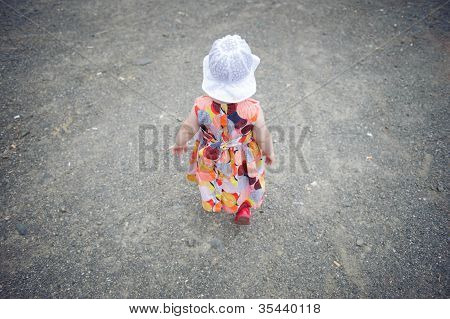 Little Girl In Dress And White Hat Walking