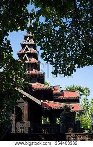 Seven-tiered spire of Bagaya Monastery seen between trees - teak wood buddhist monastery in Inwa (Ava), Myanmar