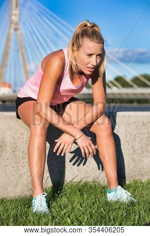 Portrait of exhausted woman sitting after running in park