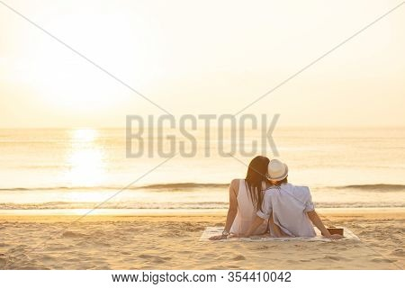 Couple In Love Watching Sunset Together On Beach Travel Summer Holidays. People Silhouette From Behi