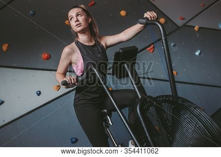 Portrait Of Young Determined Sports Woman Sitting In Bike And Doing Cycling Exercises In Dark Gym. B