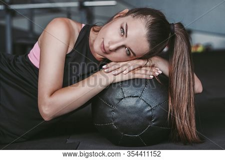 Portrait Of Confident Young Fitness Girl Lying On Medicine Ball On Floor After Functional Training I