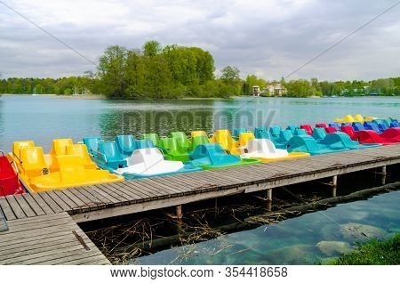 A Wooden Pier Near Lakeshore With The Row Of Colored Plastic Catamarans With Lake Water And Forest O