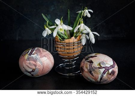 Easter Eggs Decorated With Napkin Decoupage With Pink Flowers Against A Dark Background And Snowdrop