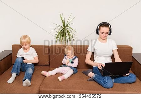 Alpha Generation Children Sit On Couch Addicted With Modern Gadgets. Overuse Of Devices .