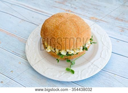 An egg salad sandwich on a plate with pea sprouts.