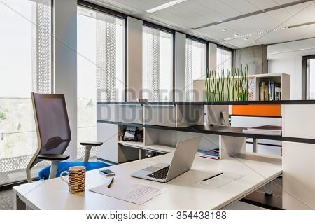 Photo of modern office meeting room with chairs tables desks and lights