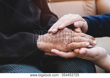 Young Man's Holding Older Grandmother Hands Feel With Love And Support Together, Care For Elderly He