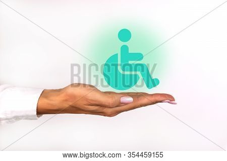 Conceptual Image, Care For Handicapped Person. Female Hand With Wheelchair Icon On White Background.