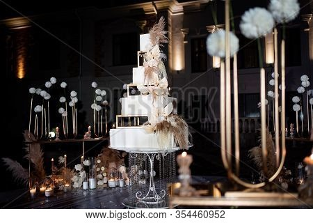 Unusual White Tiered Wedding Cake. Wedding Decor. A Traditional Treat For The Feast Of The Bride And