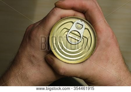 Two Hands Of An Adult Man Holds A Can Of Canned Food. Closed Tin Can With Open Key In Hand. Canned F