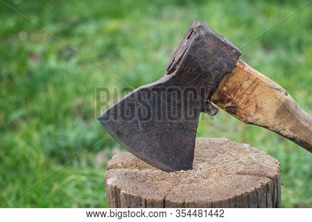 The Ax Is Stabbed With A Blade Into The Stump. Ax With Wooden Handle.