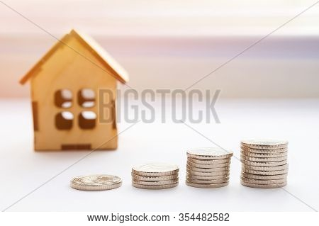 Financial Growth Concept, Real Estate Tax. Miniature House And A Stack Of Coins. Financial Growth Co