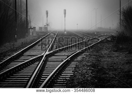 Railroad Junction With Track Switches Disappearing In Mist - Monochrome Image