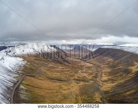 Westfjords Of Iceland Aerial Photo Of Mountain Pass Leading Down In Valley Beyond Snow Line