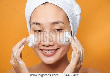 Laughing Girl Applying Moisturizing Cream On Her Face. Photo Of Young Girl With Flawless Skin On Ora