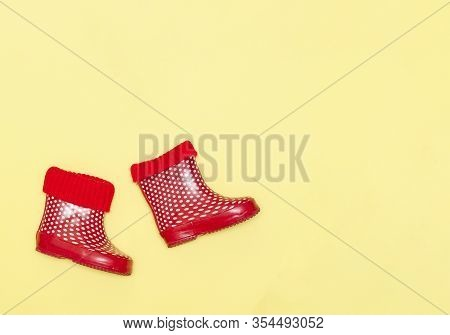 Red And White Polka Dotted Rainboots For Kids Isolated On A Yellow Background.