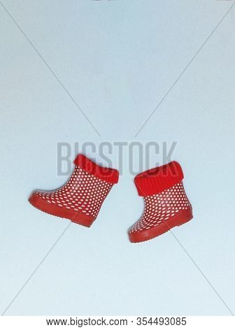 Red And White Polka Dotted Rainboots For Kids Isolated On A Gray Background.