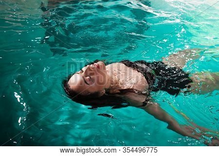 Beautiful Girl Is Relaxing In The Spa Pool,swim And Relax. Young Woman Floating In Water On The Back