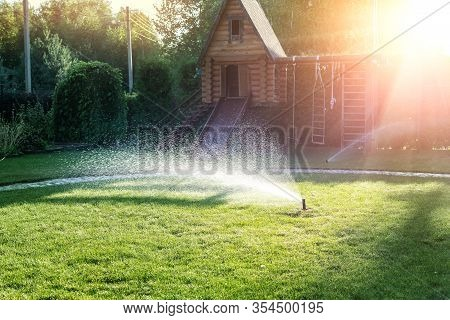 Landscape Automatic Garden Watering System With Different Sprinklers Installed Under Turf. Landscape