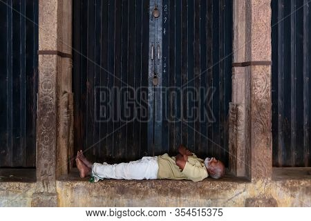 Srirangam, India - August 22, 2018: Middle Aged Man Resting Inside Sri Ranganathaswamy Temple. Is No