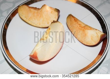 Apple Slices On A Plate Oxidized In The Air. Darkening Of The Apple On The Slice.