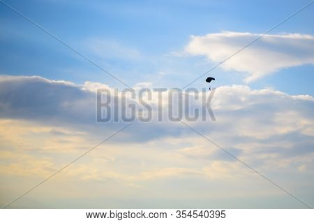 Sunset Sky, Paratroopers Soar Among The Clouds. Warm Summer Evening In Nature.