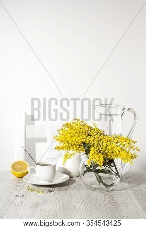 Morning Coffee On Table. Vase With Mimosa, A Symbol Of Women's Day, A Jug Of Water On A Sunny Day.
