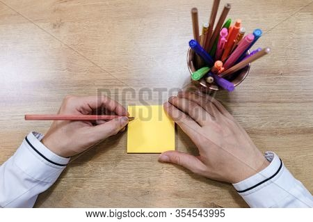 A Picture Of A Business Man With A Hand Is About To Write It On A Post-it Note.