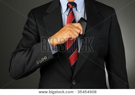 Closeup of a businessman reaching into his coat pocket to get his wallet. Horizontal format over a light to dark gray background. Man is unrecognizable.