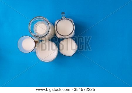 Group Bottle Of Milk On Blue Background With Copy Space.