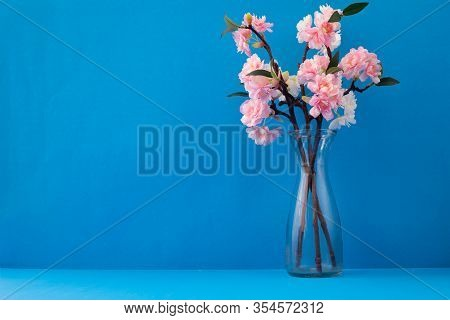Pink Flower In Glass Vase On Blue Texture Background.
