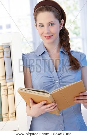 Attractive young woman standing by bookshelf at home, reading book, smiling.