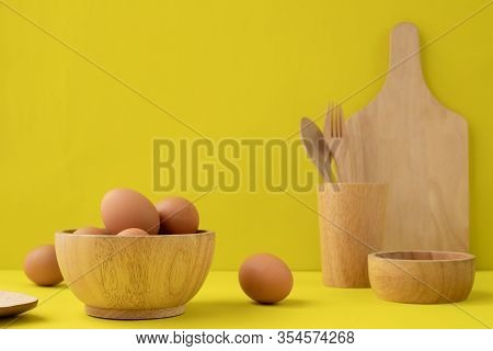 Fresh Eggs On Wooden Cup And Wooden Kitchenware On Yellow Background.