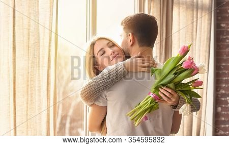 Sentimental Woman With Flowers Embracing Her Loving Husband Near Window At Home, Panorama. Space For