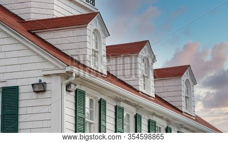 Large Coastal Home Of White Wood With A Red Roof