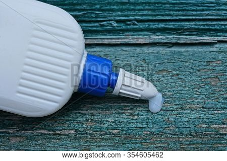 White Plastic Tube With A Drop Of Glue On A Green Wooden Board