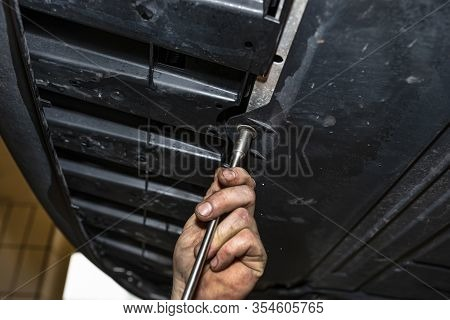 The Car Mechanic Unscrews The Bottom Plastic Engine Cover Using A Socket Wrench.