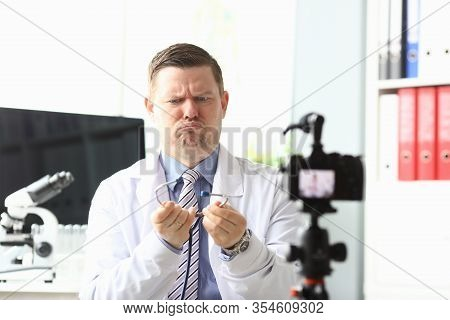 Doctor In Front Camera Is Surprised By Stethoscope. Young Doctor Tries In Simple Words To Tell Compl