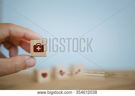 Medical Treatment / Operating System / Healthcare Concept: Hand Chooses Wooden Cube Blocks With Icon