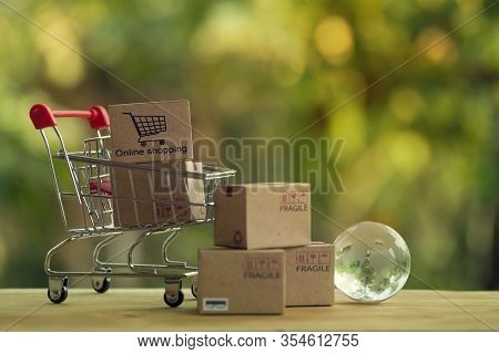Shopping Online And E-commerce Concept: Paper Boxes In Shopping Cart And Crystal Globe. Trading Mana