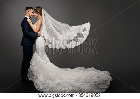 Wedding Couple, Beautiful Bride In White Dress And Long Veil, Elegant Groom Kissing Romantic Studio