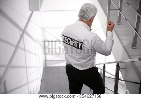 Professional Security Guard With Flashlight On Stairs Indoors