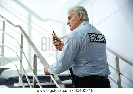 Professional Security Guard With Portable Radio Set On Stairs Indoors