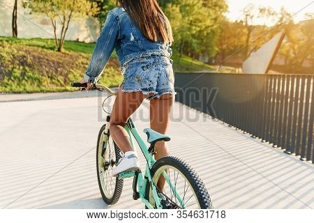 Slow Motion Of Attractive Dark-haired Hot 30-aged Girl In Tempting Jeans Clothes Riding On Bicycle O